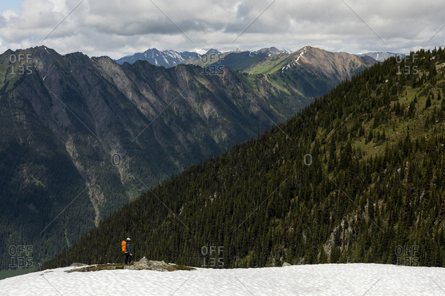 Anonymous hiker looking at majestic forested mountains on cloudy day