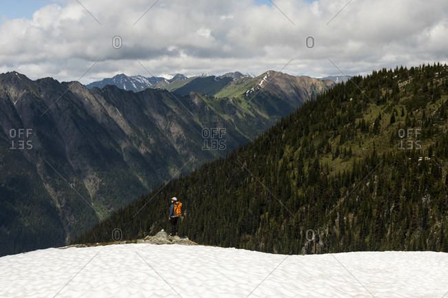 Lone female hiker with backpack looking at majestic forested mountains