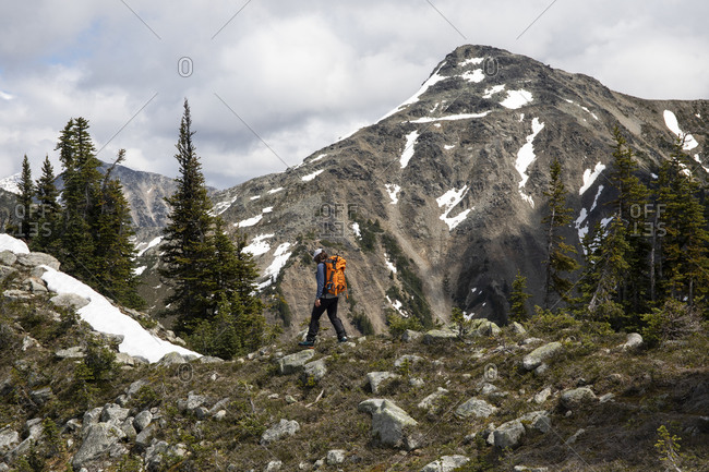 Hiker exploring forested mountains and hiking in front of rocky slope