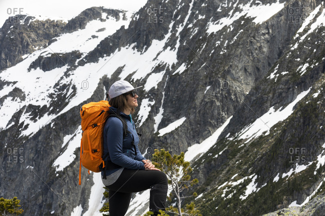 Positive happy female hiker with backpack standing on rocky snowcapped mountain slope and admiring nature while climbing in highlands in British Columbia in Canada