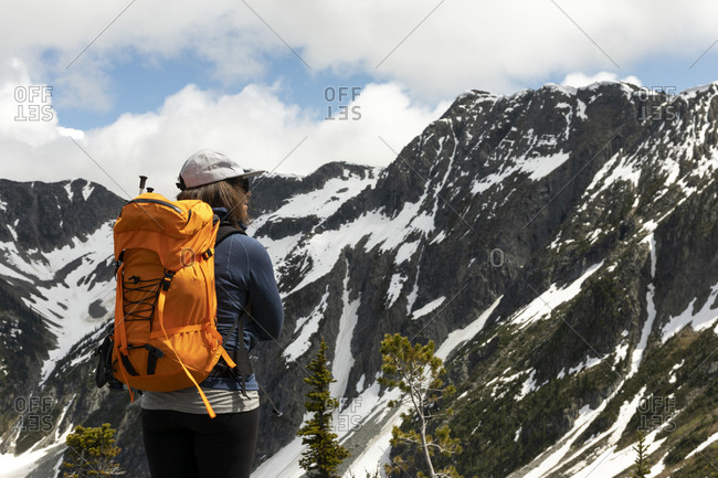 Female backpacker standing on top of mountain and observing spectacular landscape of snow covered rocky peaks during hike