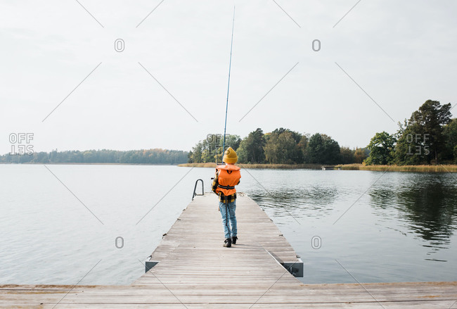 Young boy walking with a fishing rod on a jetty by the sea