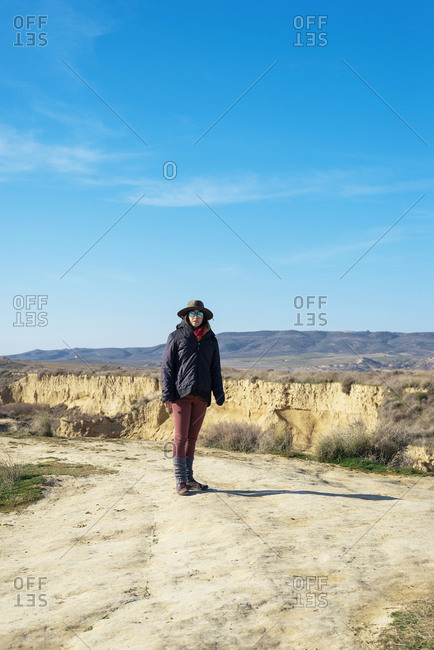 Beautiful woman with hat and sunglasses standing on desert while looking camera