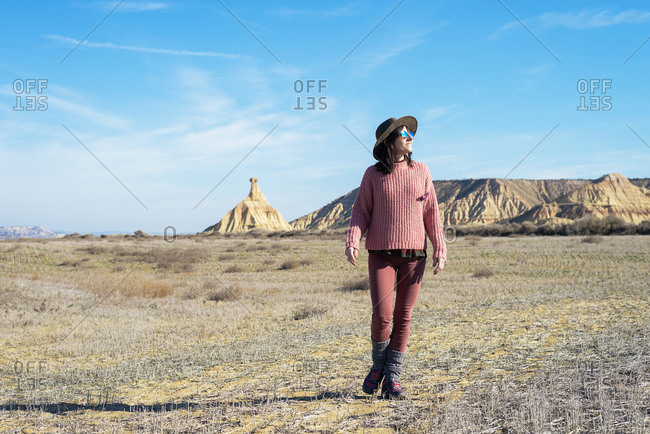 Front view of a woman in pink clothes walking in a desert in sunny day