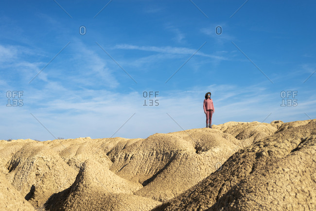 Beautiful woman with hat and sunglasses standing on desert dunes against blue sky