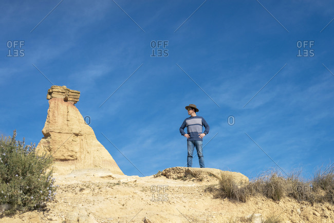 Front view of a man with hat and sunglasses standing on desert dunes against a rock peak
