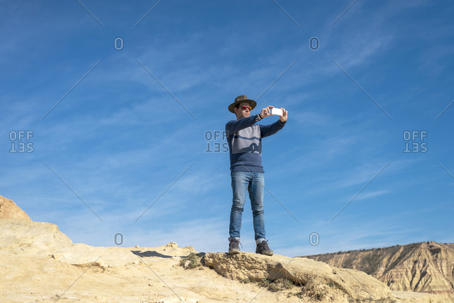 Low angle view of a man with hat and sunglasses standing while using a mobile phone to take a selfie