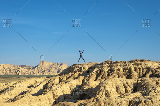 Man with sunglasses jumping with arms raised on a desertic hill against blue sky