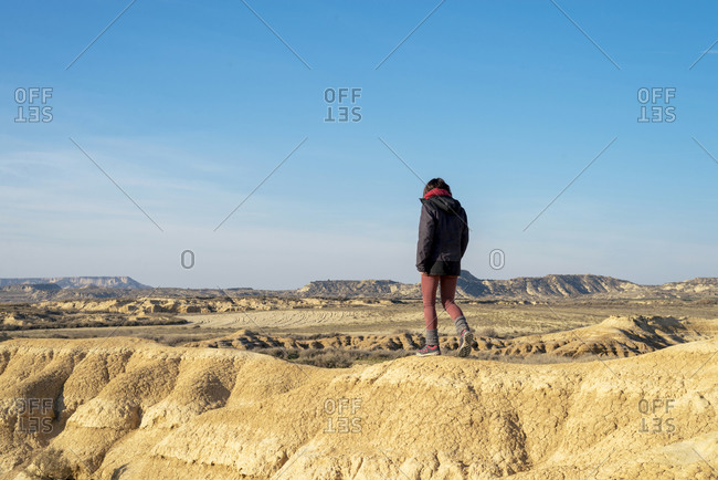Rear view of a woman walking on a hill in a desertic landscape against blue sky