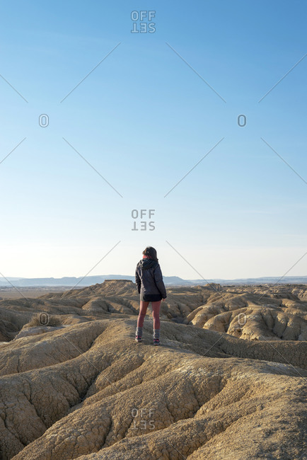 Rear view of a woman standing on a hill in a desertic landscape against blue sky