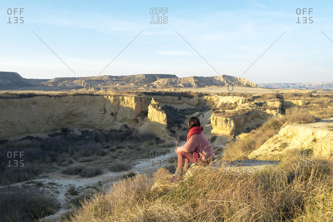 Side view of a woman with scarf sitting on top of a desert canyon while looking to horizon