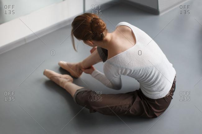 Female ballet dancer preparing to rehearsal in dance studio
