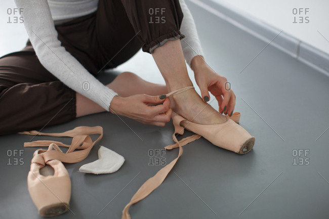 Female ballet dancer lace her pointe shoes, detail shot