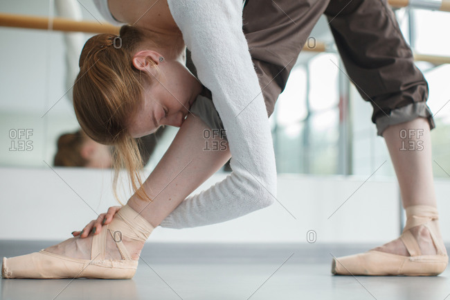 Pretty female doing ballet exercise bowing to feet with pointe shoes