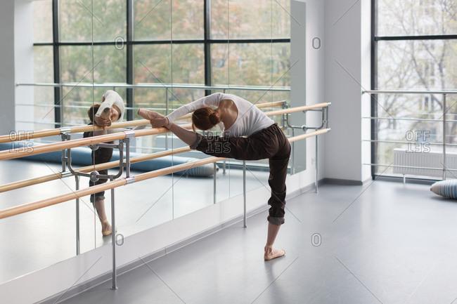 Female ballet dancer stretching on barre near mirror in dance class