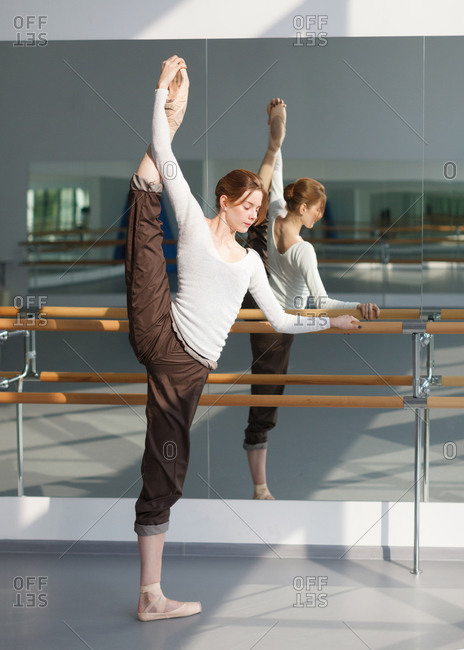 Young ballerina training near barre in choreography class