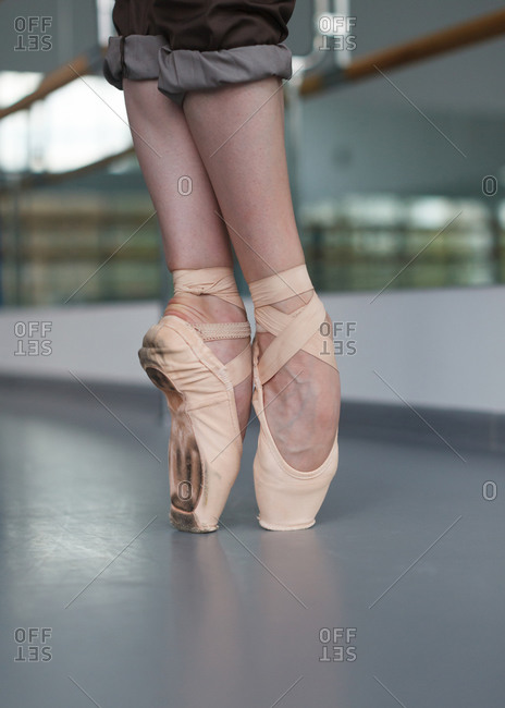 Female feet in pointe shoes standing on point, vertical shot