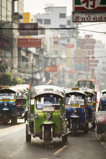 Bangkok, Thailand - January 23, 2018: Tuk tuks and taxis line up along Yaowarat Road in Bangkok's Chinatown