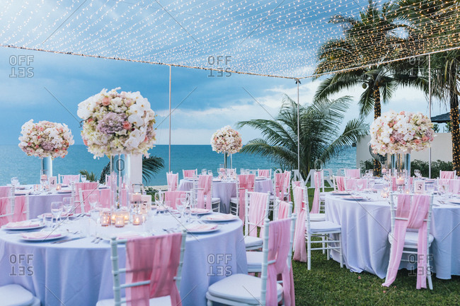 Outdoor tables at a beachfront wedding reception overlooking the Andaman Sea