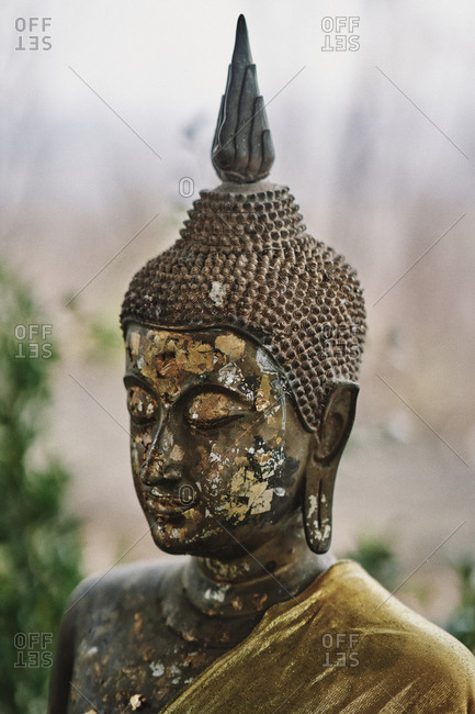 A gold leaf-flecked Buddha statue at Wat Khao Angkhan Buddhist temple in Buriram Province, Thailand