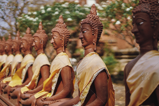 Red clay Buddha statues encircle Wat Khao Angkhan Buddhist temple in Buriram Province, Thailand