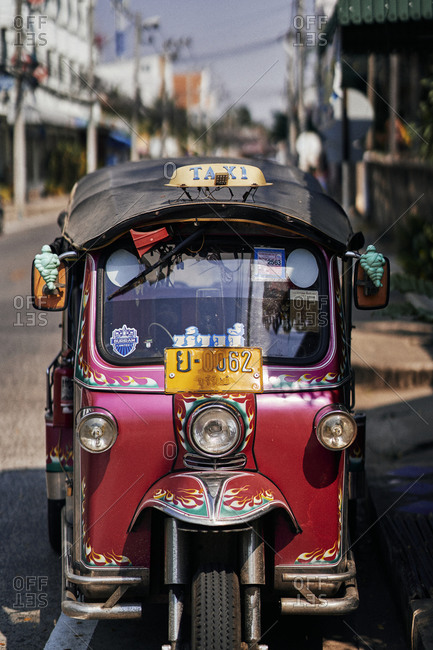 Buriram, Thailand - February 19, 2020: A red tuk tuk with flames on the streets of Buriram town