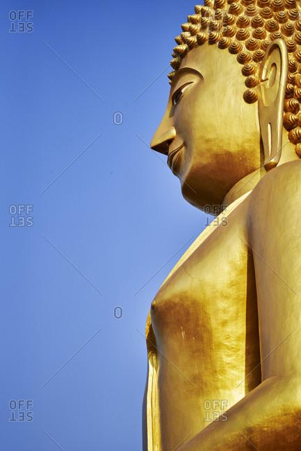 A giant golden Buddha statue presiding over Khao Kradong Forest Park in Buriram, Thailand
