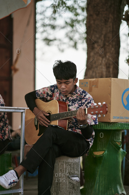 Buriram, Thailand - February 19, 2020: A young man practicing guitar atop Khao Kradong Forest Park in Buriram, Thailand