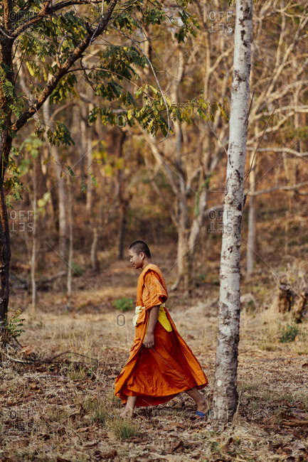 Buriram, Thailand - February 19, 2020: A novice monk walks through a wooded area on the grounds of Khao Kradong Forest Park