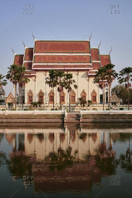 Buriram, Thailand - February 20, 2020: Wat Klang Phra Aram Luang in central Buriram, reflected in its front moat