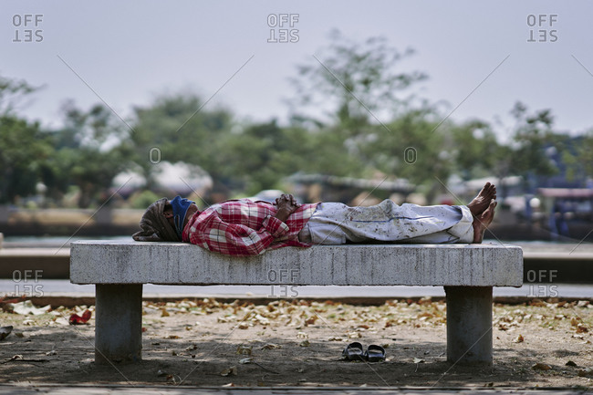 Buriram, Thailand - February 20, 2020: A worker takes an afternoon nap on a bench near Khlong La Lom
