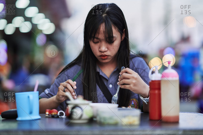 Buriram, Thailand - February 21, 2020: A young girl eats an early dinner at a roadside night market near the King Rama I monument in