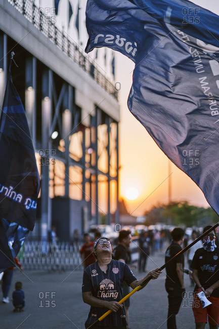Buriram, Thailand - February 22, 2020: A Buriram United fan waves a flag at sunset at Chang Arena before a big football game