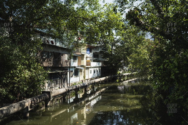 A small canal with houses along its sides running through the old town in Bangkok, Thailand