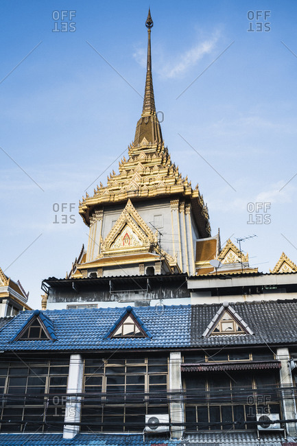 A temple spire rises over local shophouses in the Bangrak neighborhood of downtown Bangkok, Thailand