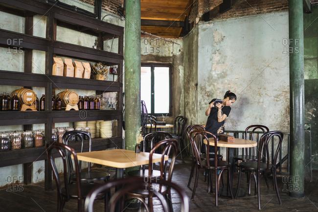 Bangkok, Thailand - April 5, 2019: A waitress checks on a downstairs order at Sarnie's cafe and restaurant in Bangkok's old town