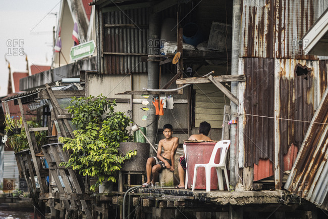 Bangkok, Thailand - April 5, 2019: Two young boys sit outside their home along the Chao Phraya river and its byways