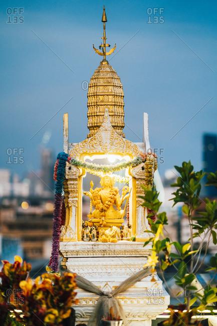 A small Buddha statue and altar at dusk in Talad Noi, Bangkok