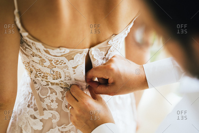 A young bride has her dress zipped up before her ceremony