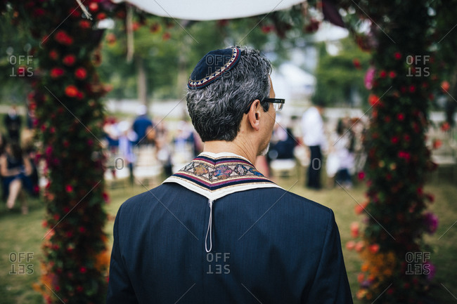 A rabbi presides over a traditional Jewish wedding in an outdoor garden