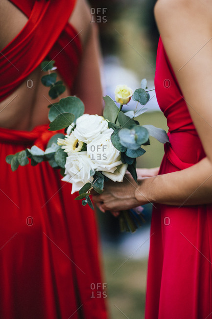 Bridesmaids in red dresses holding white flowers at a garden ceremony