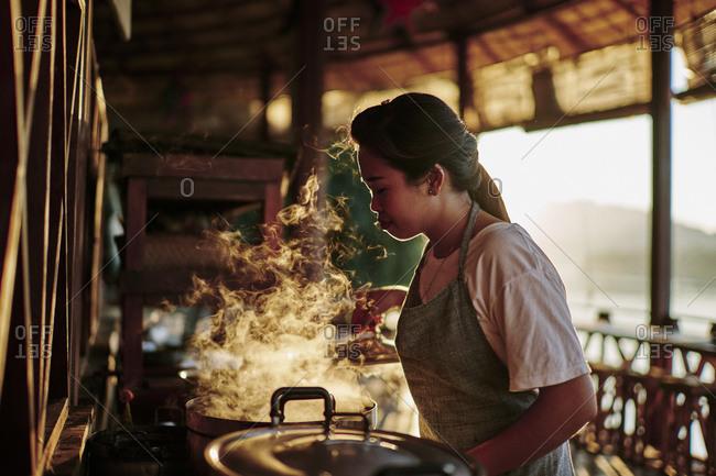 Luang Prabang, Laos - November 13, 2020: A young woman checks on a boiling pot of dye for silk at Mekong Villas