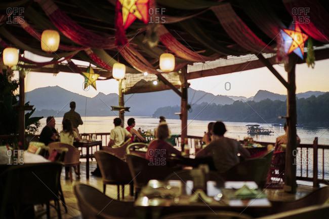 Luang Prabang, Laos - November 13, 2020: Crowds gather at an outdoor restaurant at sunset along the river at Mekong Villas