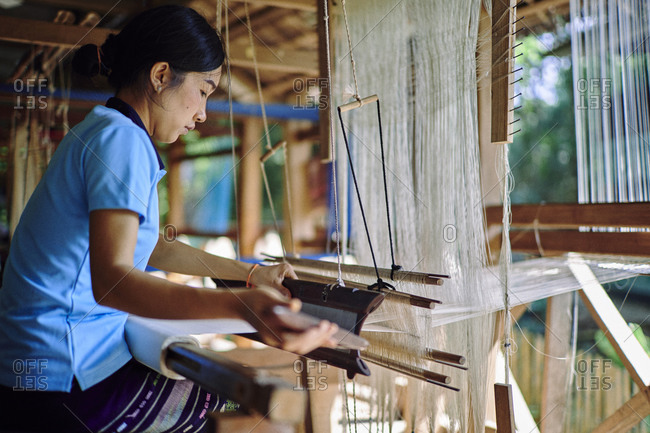 Luang Prabang, Laos - November 13, 2020: Young woman works on a traditional loom weaving silk scarves and blankets at a workshop at the Mekong Villas