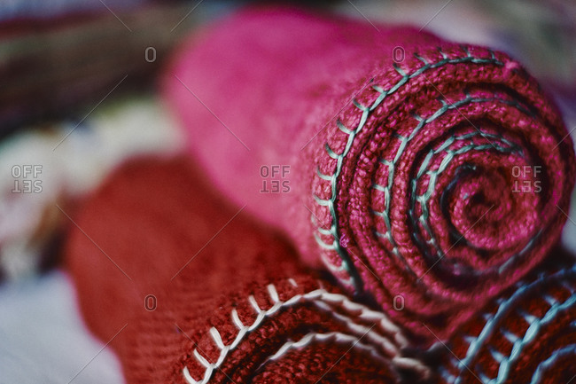 Rolls of colorful hand-woven scarves and blankets close up