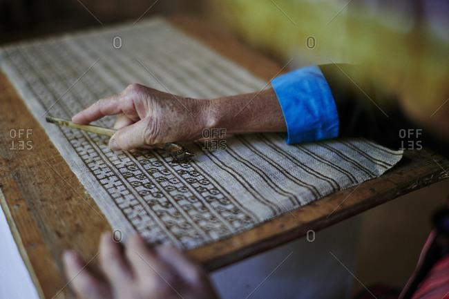 An older Lao woman draws designs on fabric using a traditional batik method in Luang Prabang, Laos