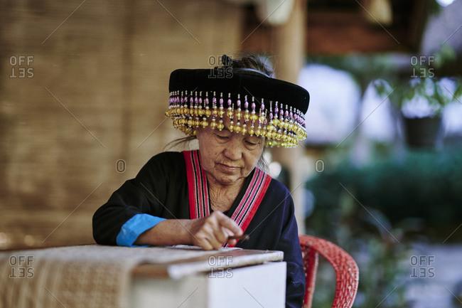 Luang Prabang, Laos - November 13, 2020: An older Lao woman draws designs on fabric using a traditional batik method