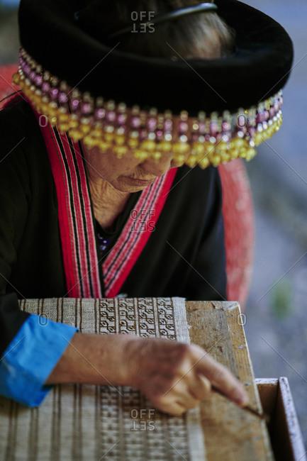 Luang Prabang, Laos - November 13, 2020: Close up of an older Lao woman draws designs on fabric using a traditional batik method