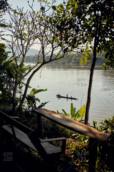 A lone fishing boat drifts down the Mekong River in the later afternoon in Luang Prabang, Laos
