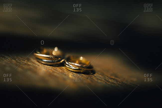Gold wedding rings on a wooden table in a ray of afternoon sun
